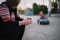 grandmother sits and drinks coffee watching her granddaughter while driving an electric car in the yard.