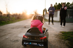 Girl driving electric car at sunset and grandparents are waiting for her.
