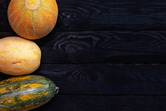 Three sweet melons on the dark board