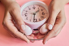 Female checking a time. Woman hands taking an alarm clock