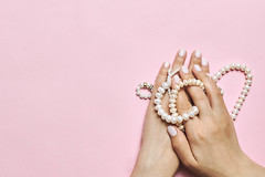 Beautiful female hands with manicure holding pearls