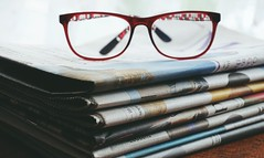 Red framed eyeglasses on newspapers - Credit to https://homegets.com/