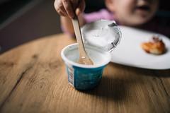 Little girl having breakfast. Wooden spoon closeup.