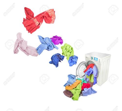 Colored laundry flying from washing machine, isolated on white background