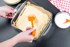 A woman spreads the dough in a baking tray with a kitchen spatula