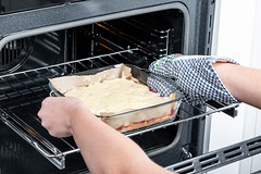 A woman puts a raw pie in an open electric oven