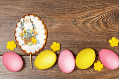 Easter gingerbread and multicolored chicken eggs on a wooden background, top view