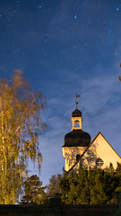 Authentic German protestant church at night with the starry sky above it