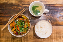 Healthy vegan meal, Vietnamese recipe (Đậu Hũ Sốt Me), top view on a wooden table: diced organic tofu pan-fried with carrots, onions, mushrooms, shiitake-tamarind sauce and herbs, served with chopsticks, rice and a hot drink with ginger root, lemon and mi