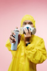 Person in yellow protection suit holding a spray can - Credit to https://homegets.com/