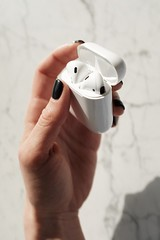 Person holding white apple airpods - Credit to https://homegets.com/