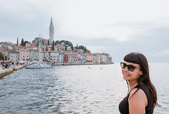 Girl standing by the sea with Rovinj city in the background