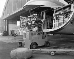1964 Loading equipment into RNZAF Bristol Freighter NZ5910 using forklift SV181, at RNZAF Station Whenuapai for a Technical Support Unit exercise at Kaitaia, 10 Dec 1964.