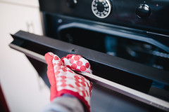 Opening the oven with protective gloves