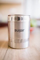 Closed sugar can on wooden desk closeup.
