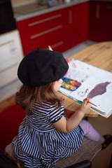Little girl artist in striped glamour dress.
