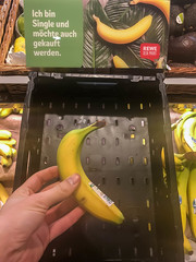 Hand of a customer buying a banana sold individually at a supermarket