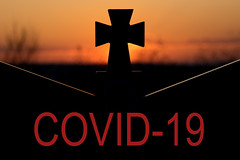 Cross on a gravestone and COVID-19 text