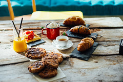 Cookies, fresh orange juice, coffee and croissant on wooden and rustic table.