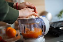 Woman making fresh orange juice in tje kitchen.