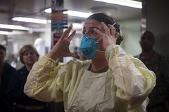 A Sailor demonstrates how to properly fit an N95 respiratory protective device aboard USNS Comfort (T-AH 20)