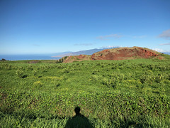 Lanai, West Maui Mountains, and a red hill