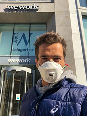 Coronavirus and WeWork. Men with FFP3 mask in front of office