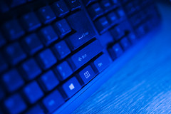 Black keyboard with blue neon light closeup. Focus on Shift button.