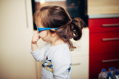Little girl In blue sunglasses at home.