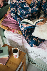 Young woman reading a book and drinking coffee in bed.