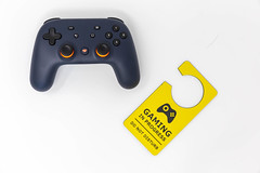 """Basic equipment for gaming: Stadia video game controller and yellow door hanger """"Gaming in progress - do not disturb"""", seen from above with white background"""