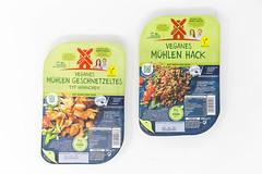 Zwei vegane Produkte auf Basis von Soja von Rügenwalder Mühle: veganes Mühlen Geschnetzeltes (Typ Hähnchen) und veganes Mühlen Hack in Verpackung vor weißem Hintergrund