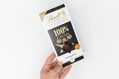 Hand holds the new Lindt Excellence chocolate bar with 100% pure cacao on a white background