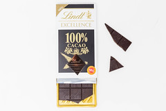 New product by Lindt: Lindt Excellence 100% cacao chocolate bar, package open with some loose pieces on white background