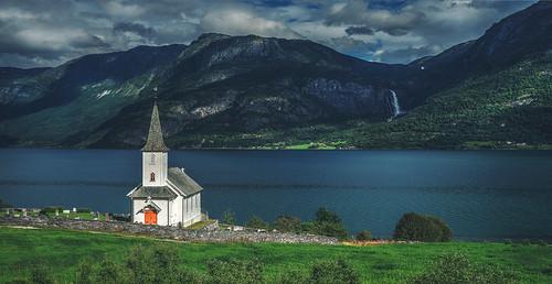 Little white Nes Church and the 218 meters high Feigumsfossen waterfall in Høyheimsvik