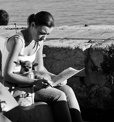 Woman completely absorbed reads a working document. Meanwhile the dog keeps watching any stranger (like the photographer)
