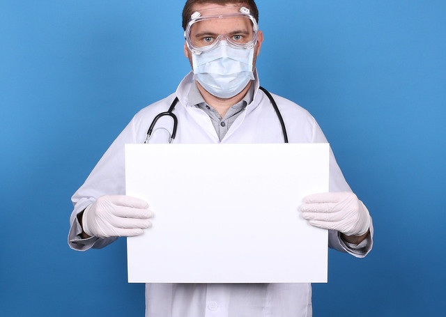 Doctor holding blank sign at blue background