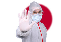 Doctor or Nurse Wearing Medical Personal Protective Equipment (PPE) Against The Flag Of Japan
