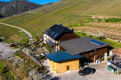 Drohnenaufnahme von großem Landhaus mit weinbewachsenem Hügel im Frühling