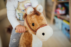 Little girl playing with his toy horse closeup.