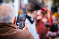 Elderly man live streaming an event with his phone