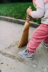 Little girl cleans the yard with broom.