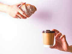 Person hand holding disposable cup and croissant - Credit to https://homegets.com/