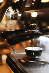 Black espresso maker with cup - Credit to https://homegets.com/