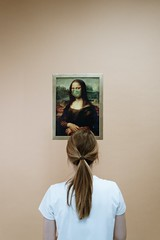 Woman in white shirt looking at a painting of mona lisa  - Credit to https://homegets.com/