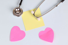 Red heart with stethoscope and yellow sticky note