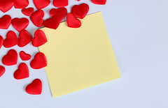 Blank paper note and red hearts on blue paper background