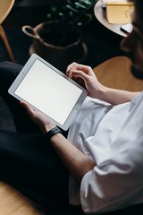 Person holding white tablet computer - Credit to https://homegets.com/
