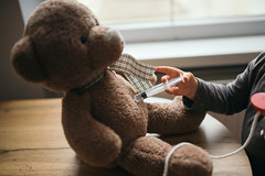 Little girl doing injection to sick teddy bear toy.