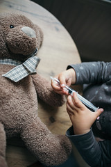 Little girl doing injection to sick teddy bear